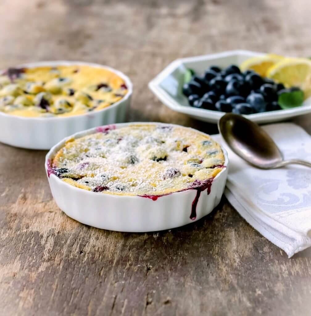 Blueberry Lemon Clafoutis in a white dish sitting on a table