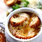 French Onion Soup in a white bowl with croutons and cheese on top